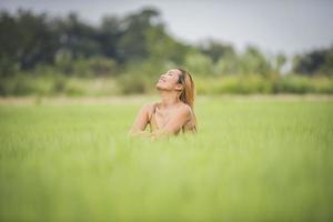 ung kvinna som sitter må bra i gräsfält. foto