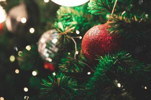 närbild av dekorera prydnad på julgran med bokeh -ljus foto