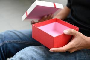 man öppnar tom presentförpackning foto