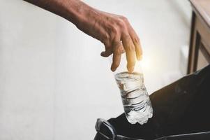 närbild av handen som kastar sopor i svart påse foto