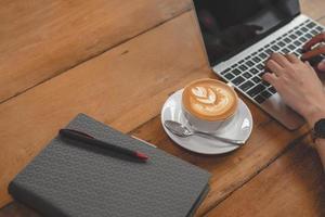 närbild av kaffekopp med anteckningsbok och kvinnahänder med bärbar dator foto