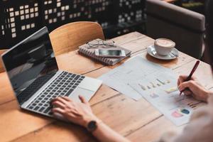 närbild av affärskvinna som arbetar med dokument och bärbar dator på kontoret foto