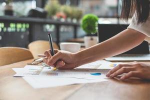närbild av affärskvinna hand skriva sammanfattande rapportdata foto