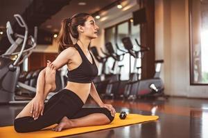 kvinna gör böjda ben yoga i fitness träning gym foto