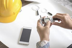 konstruktionsingenjör som mäter med vernier -tjocklek foto