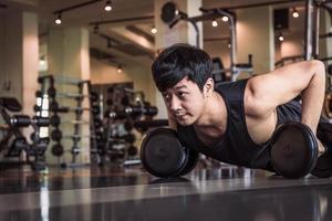 porträtt av asiatisk fitness man gör pushing upp övning med hantel foto