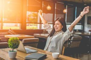 skönhet asiatisk kvinna som höjer två händer efter avslutat jobb foto