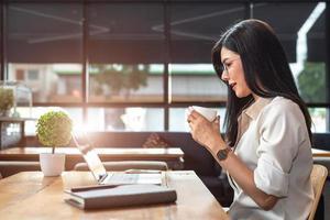 asiatisk arbetskvinna som använder bärbar dator och dricker kaffe på café foto