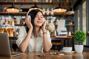 glad asiatisk kvinna som kopplar av och lyssnar på musik foto