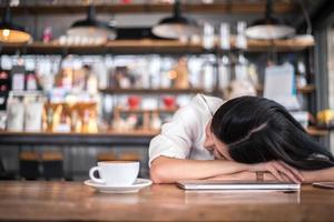 asiatisk kvinna vilar och sover i ett kafé foto