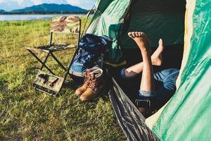 närbild av kvinnaben som kopplar av i campingtält med bergssjö foto