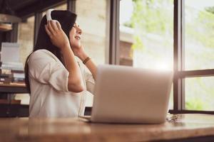 glad asiatisk kvinna som kopplar av och lyssnar på musik i kaféet foto