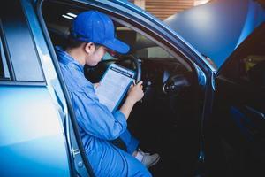 mekaniker håller urklipp och kontrollerar inuti bilen för underhåll foto