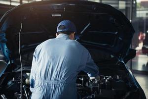 bilmekaniker som öppnar motorhuven för intern kontroll till underhåll foto