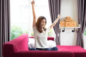 glad ung asiatisk affärskvinna som sitter på den röda soffan och sträcker sig foto