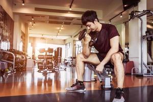 asiatisk sport man lyft hantel på fitness bänk med gym foto