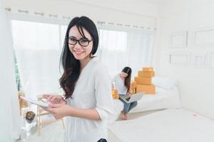 skönhet asiatisk kvinna tittar och använder surfplatta för att kontrollera ordning foto