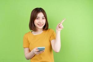 ung asiatisk tjej poserar på grön bakgrund foto