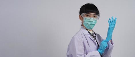 bär handskar. asiatisk läkare bär blå gummi nitril händer handske. foto