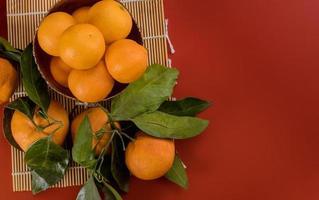 mandarin apelsin med grönt blad med korg isolerad på röd bakgrund foto