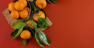 mogna ljusa råa mandariner på gren med gröna blad i en skål foto