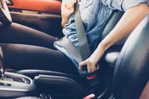 asiatisk kvinna som spänner fast säkerhetsbältet i bilen, säkerhetskoncept foto
