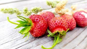 närbild jordgubbar med torra gula kvistar av spannmål foto