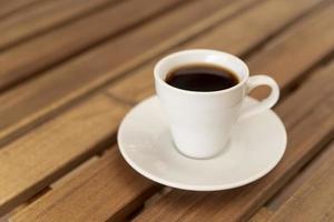 kopp svart kaffe på träbord foto