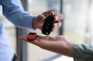 närbild av byte av bilnycklar och modellbilar. foto