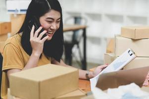kvinna som säljer produkter online pratar i telefon och kontrollerar lager, foto