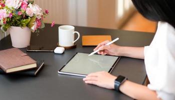 unga kvinnor skriver på modern surfplatta med en digital penna på ett svart skrivbord. foto