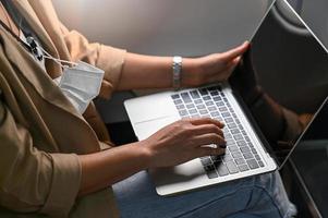 ung kvinna som använder en bärbar dator under resan. foto