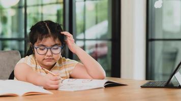 ett barn flicka i glasögon ritar i en anteckningsbok med en surfplatta. foto