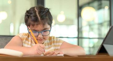 barnflicka med glasögon studerar hemma med allvarligt uttryck. foto