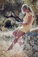 en barfota blond kvinna i en gul sommarklänning foto