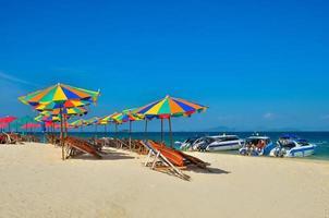 phuket, thailand, 2020 - stolar och paraplyer på en strand med människor och båtar foto