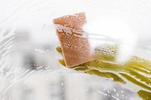 kvinna rengöring fönster med svamp foto