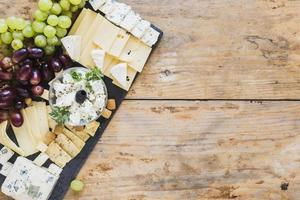 ost med druvor på svart skifferbord foto