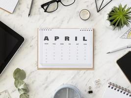 ovanifrån av skrivbordet med aprilkalender foto
