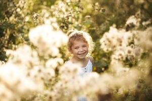 glad glad liten flicka bland vildblommor foto