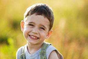 glad liten pojke leende foto