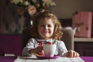 glad tjej sitter vid bordet foto