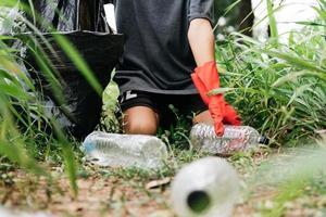 pojke man hand plocka upp plastflaska i skogen. miljö koncept. foto