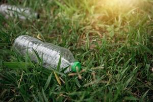 plastflaska på grönt gräs. ekologi miljöföroreningar. foto