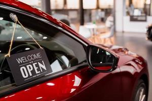 öppen bil med röd bil i återförsäljare för dörr bilidéer låsa upp frihet turistresor för livsstilskund från säljare tecken välkomna ny normol under coronavirus sjukdom covid-19 låsa upp lockdown foto