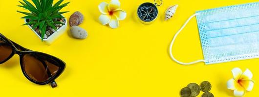 säkra resor under coronaviruspandemin. nytt normalt. medicinsk mask och solglasögon på en gul bakgrund. foto