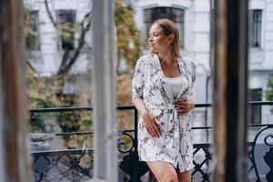 glad gravid kvinna i badrock kramar magen på terrassen foto