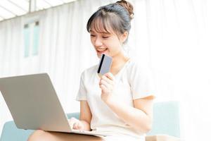 porträtt av ung flicka som sitter på soffan hemma med hjälp av bärbar dator och håller bankomatkort i handen foto