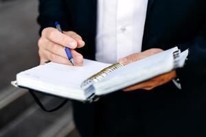 närbild manlig hand med en penna och anteckningsbok. skrivit en anteckning. - bild foto