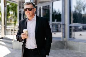 porträtt av senior affärsman som håller en kopp kaffe och ler. - bild foto